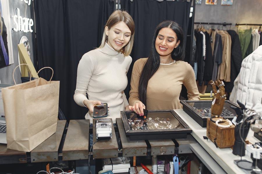 Dos mujeres pagando en una tienda con una app de su smartphone