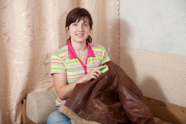 Mujer limpiando una campera de cuero