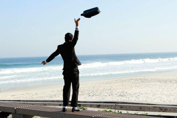 Hombre tirando el maletín en la playa tras abandonar su empleo.
