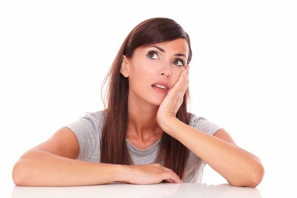 Mujer tomándose la mejilla. Algunos sintomas de mala circulación producen cambios de color en la piel.