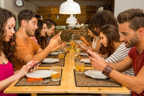 Reunión de personas usando el movil, una de las normas de protocolo social que no se cumplen