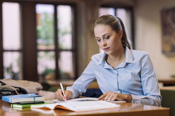 Mujer trabajando en biblioteca con las reglas para ser eficiente
