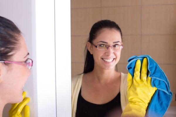 Limpiando el espejo del baño con un trapo suave