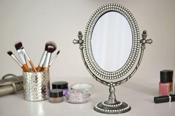 Espejo antiguo plateado ubicado en una mesa