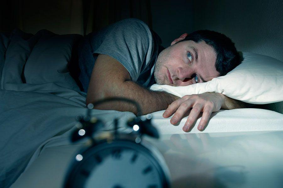Hombre en la cama despierto, con problemas para dormir o con insomnio.