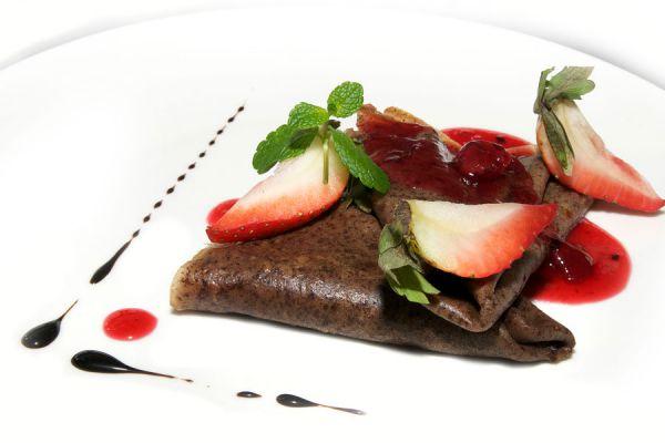 Crepes de chocolate decorados con trozos de frutilla y salsa dulce