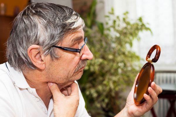 Persona de la tercera edad observando su doble mentón. Se puede reducir con ejercicios simples.