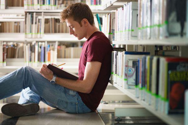 Joven en biblioteca con un libro en mano estudiando a solas.