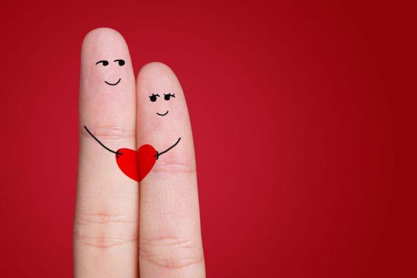 Dedos con garabatos dibujados y un corazón