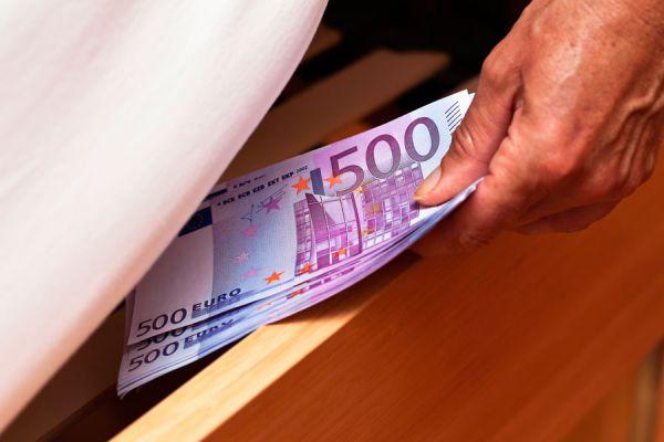 Mano de hombre guardando dinero en un cajón