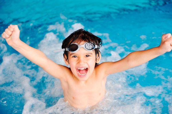 Niño en piscina practicando natación