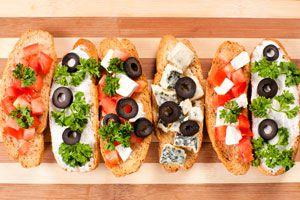 Bruschettas de pan con queso, aceitunas, tomates y hierbas frescas