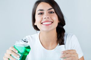 Mujer sonriente usando enjuague bucal